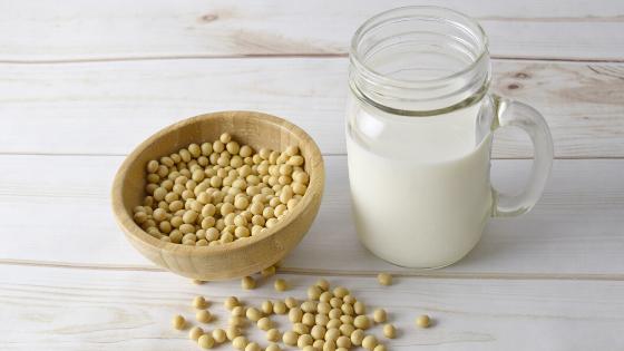 """obrazek wyróżniający do artykułu """"roślinne zastępniki mleka"""", na którym po lewej stronie znajduje się drewniana miska wypełniona ziarnami, a po prawej słoik wypełniony mlekiem"""